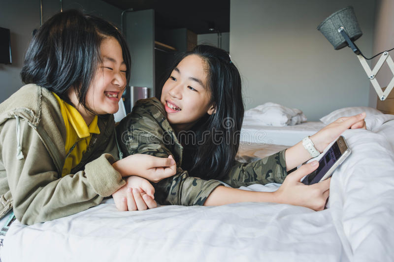 Happy smiling Asian kids on bed playing smart phone stock photos