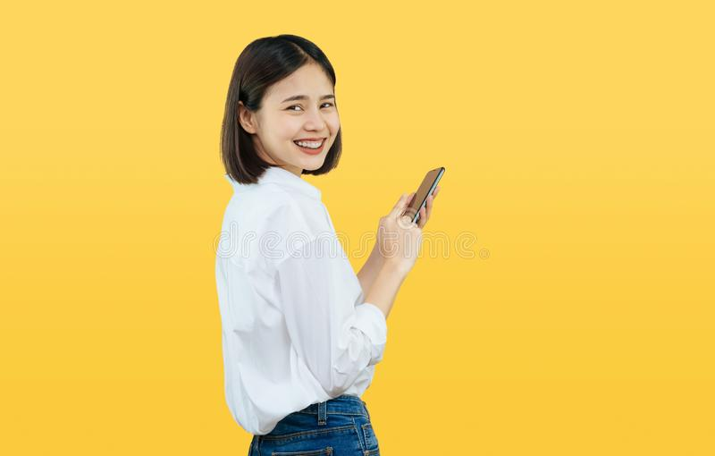 Happy smiling Asian woman with holding smart phone on yellow background. royalty free stock photography