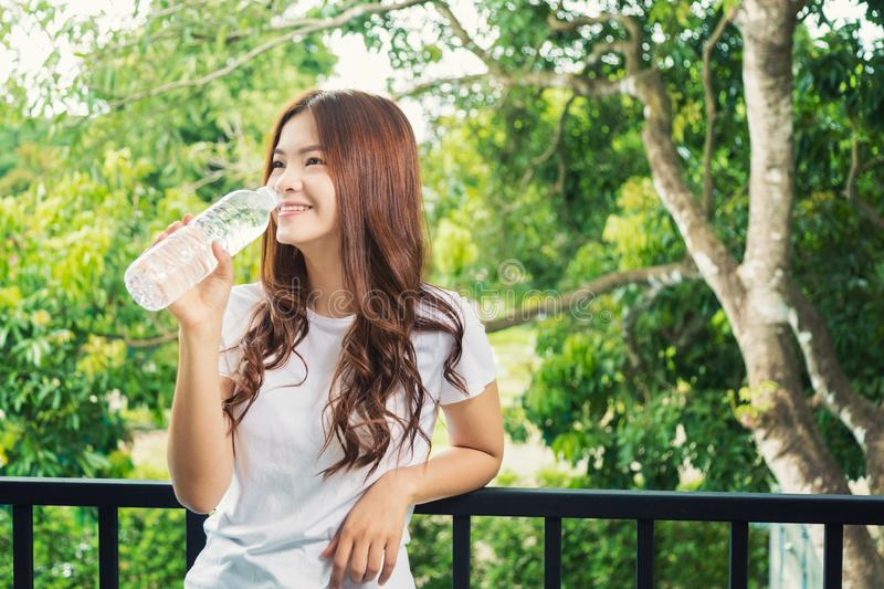 Happy smiling asian woman holding water bottle to drink, standing on her balcony royalty free stock images