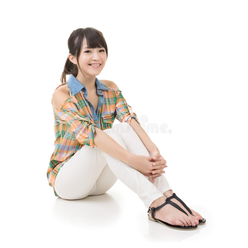 Happy smiling asian woman sit on ground. Full length portrait on white background royalty free stock images