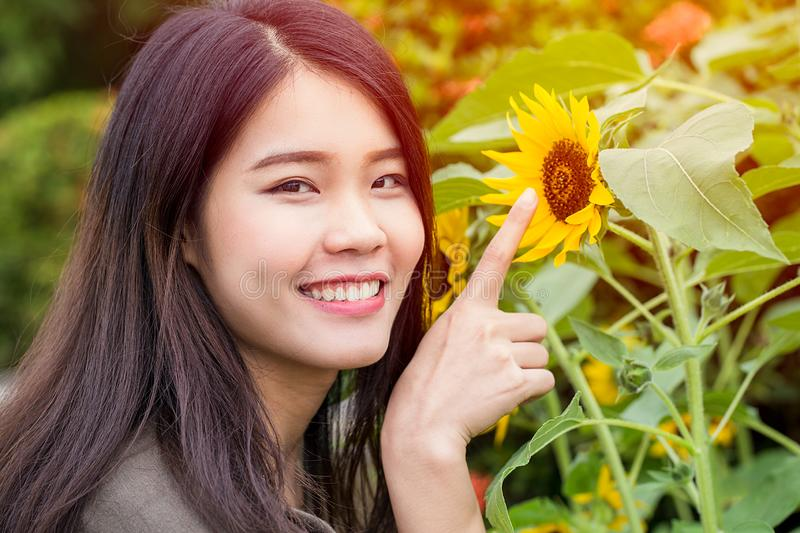Happy smiling asian young teen with sunflower stock images