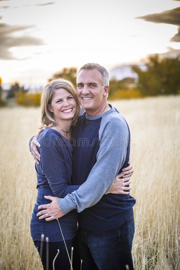 Happy and smiling attractive mature couple portrait outdoors. A Beautiful Middle-Aged Couple portrait outdoors. Smiling and looking at the camera with a happy royalty free stock images