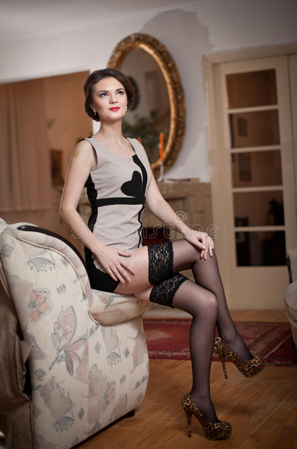 Happy smiling attractive woman wearing an elegant dress and black stockings sitting on the sofa arm. Beautiful young sensual girl stock photography