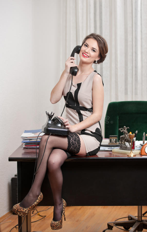 Happy smiling attractive woman wearing an elegant dress and black stockings talking by phone in an office scenery. Beautiful girl stock photos