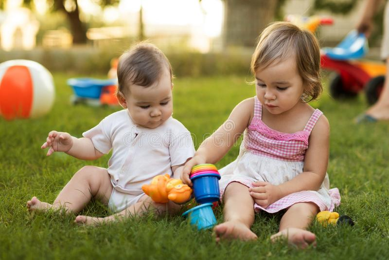 Happy Smiling Baby Brother and Toddler Sister Playing with Toys Together in Backyard Garden in Summer royalty free stock photos