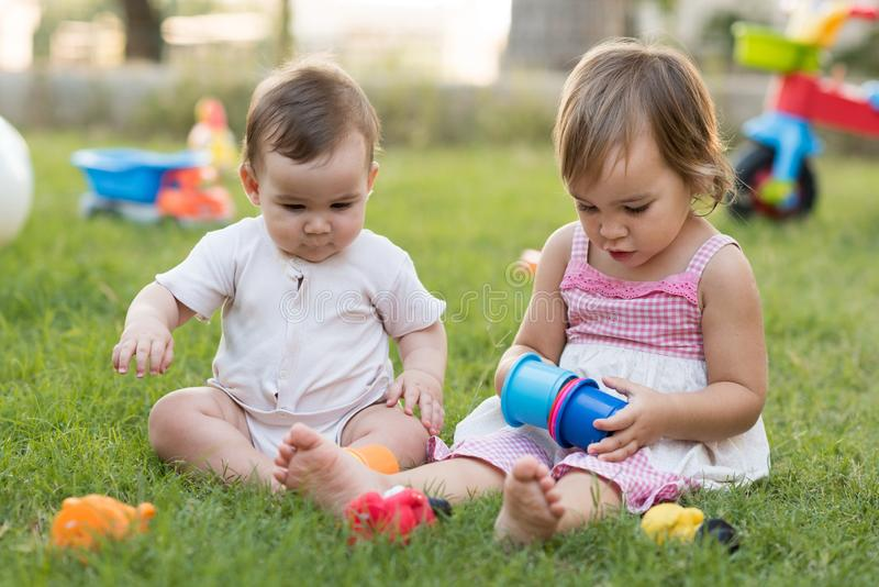 Happy Smiling Baby Brother and Toddler Sister Playing with Toys Together in Backyard Garden in Summer Season royalty free stock photography