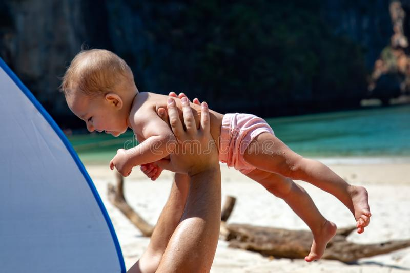 Happy smiling baby in dad arms. On a tropical beach. Sunny day, father throws up infant toddler, hold on hands. Child enjoy.  royalty free stock image