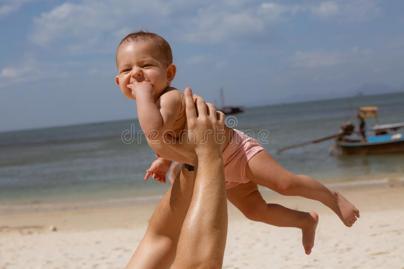Happy smiling baby in dad arms. On a tropical beach. Sunny day, father throws up infant toddler, hold on hands. Child enjoyed.  royalty free stock photography