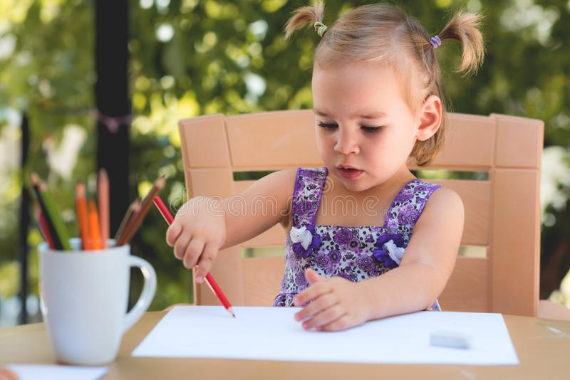 Happy Smiling Baby Girl Drawing Pictures Outdoors royalty free stock photo