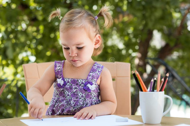 Happy Smiling Baby Girl Drawing Pictures Outdoors stock photography