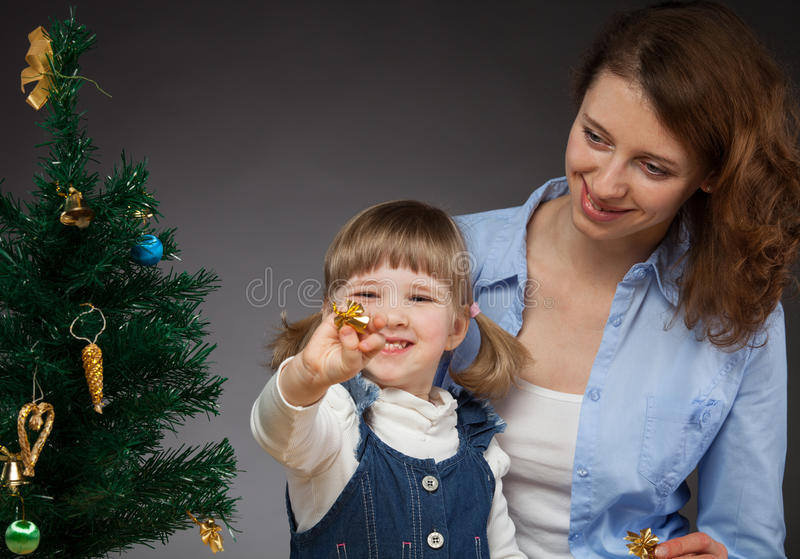 Happy smiling baby girl and her mummy decorates the Christmas tr stock photos