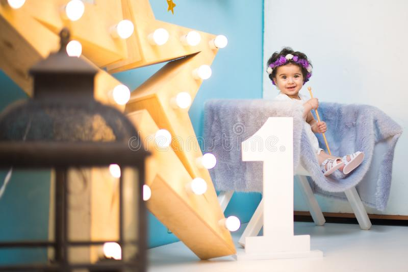 Happy smiling sweet baby girl sitting on armchair with shining light star, Birthday girl, One year old. Happy smiling baby girl sitting on armchair with shining stock photography