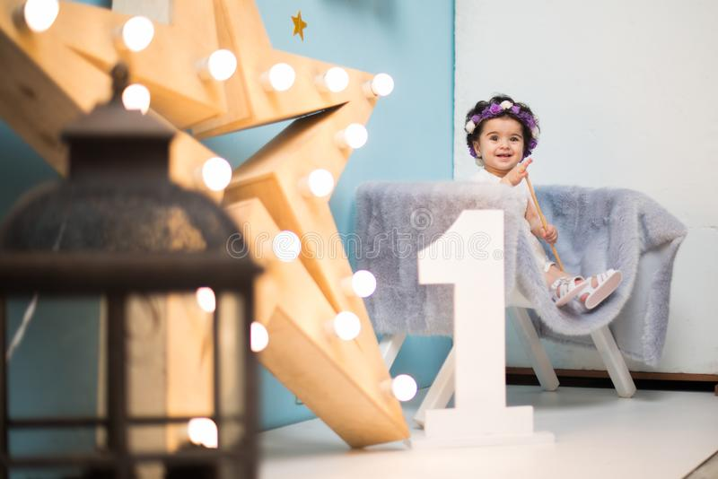 Happy smiling sweet baby girl sitting on armchair with shining light star, Birthday girl, One year old. Happy smiling baby girl sitting on armchair with shining stock photos