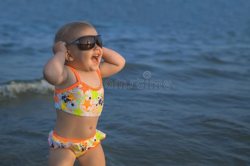 Happy smiling baby girl with sunglasses at the beach royalty free stock image