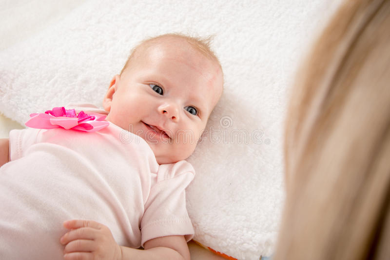 Happy smiling baby looking at mother. A two-month baby lying on his back on the bed, sitting next to the child and mother looking at her royalty free stock images