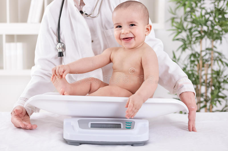 Happy smiling baby in pedrician office, measuring weight stock photos