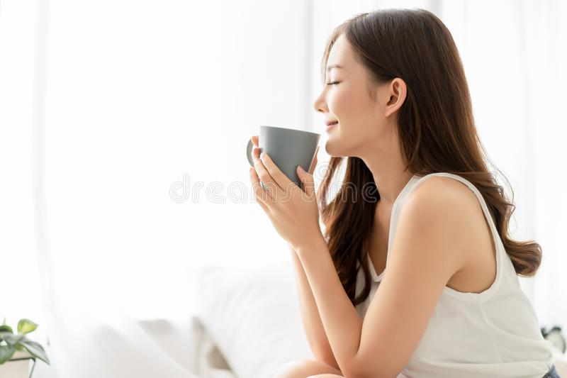 Happy smiling beautiful Asian woman enjoying first morning and smelling aroma of cup of coffee tea in her bedroom.Enjoying free royalty free stock photo