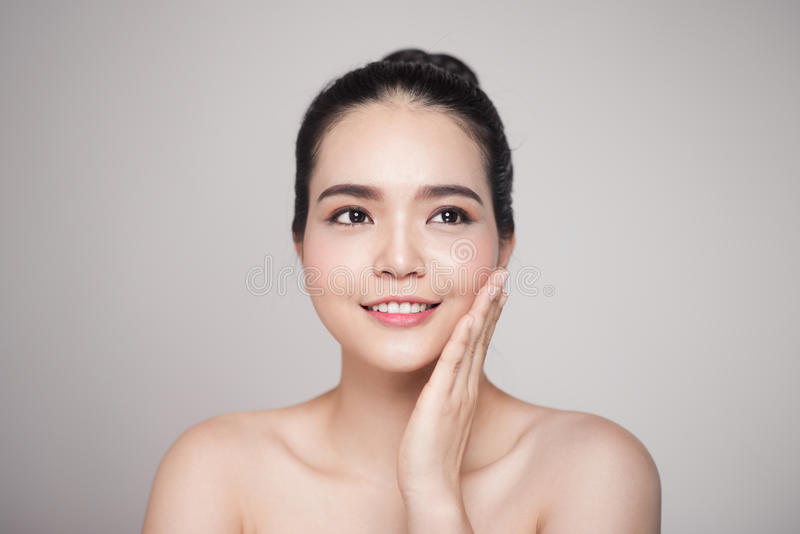 Happy smiling beautiful asian woman touching her face. royalty free stock photo