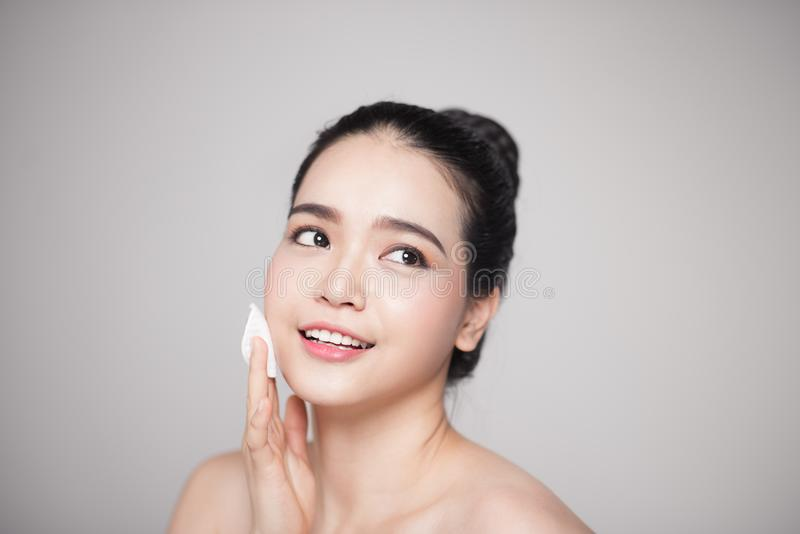 Happy smiling beautiful asian woman using cotton pad cleaning sk royalty free stock image