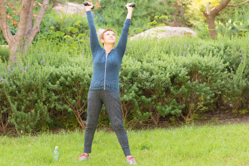 Happy smiling beautiful elderly woman doing sport exercises with dumbbells in a park on a sunny day. royalty free stock photos