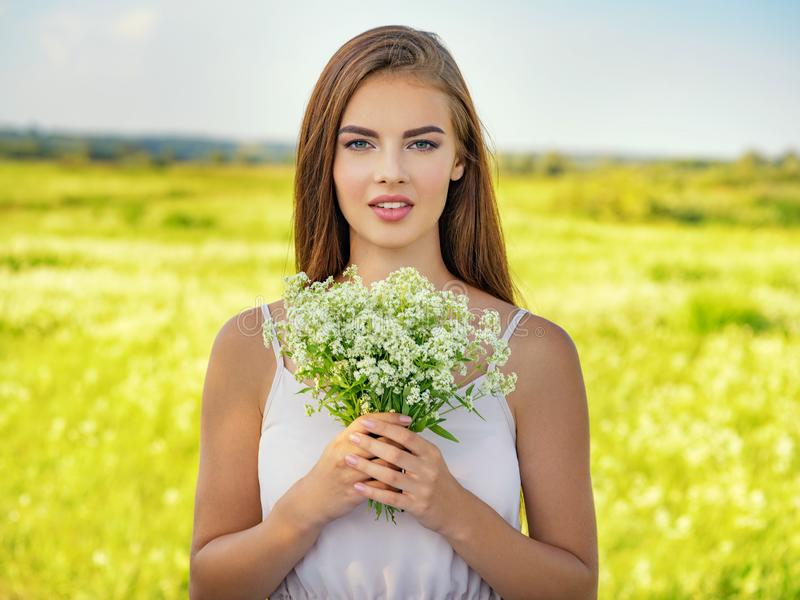 Happy and smiling beautiful woman outdoor with flowers in hands royalty free stock photos