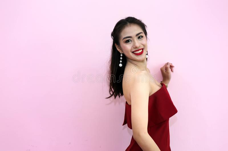Happy smiling beautiful young woman in red party dress.  stock photography