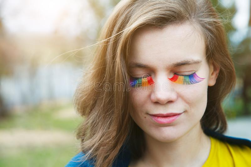Happy smiling beautiful young woman with rainbow lgbtq eyelashes stock images