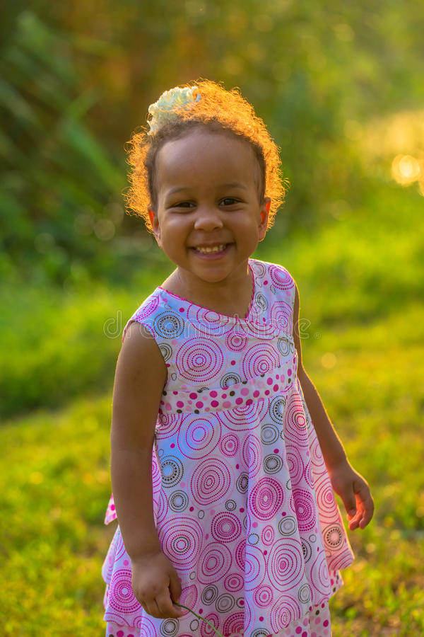 Happy smiling black baby girl outdoors. stock photos