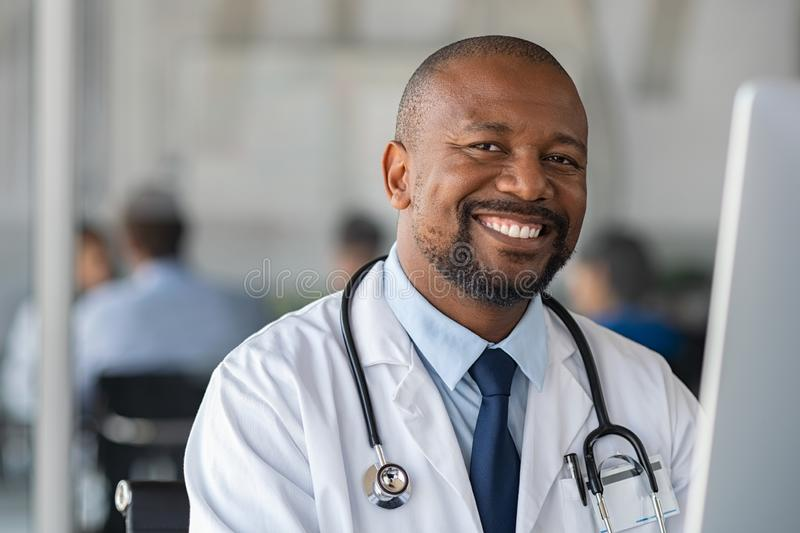 Happy smiling black doctor looking at camera stock photos