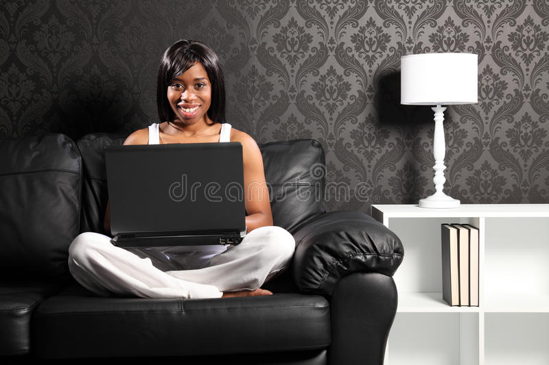 Happy smiling black woman on sofa surfing internet. Beautiful smiling young black woman sitting cross legged on leather sofa at home, surfing the internet with stock photography