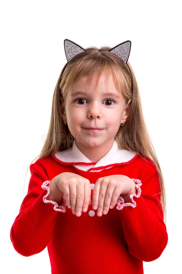 Happy smiling blond girl in a red dress with a cat ears band on the white isolated background, holding her hands like a royalty free stock image