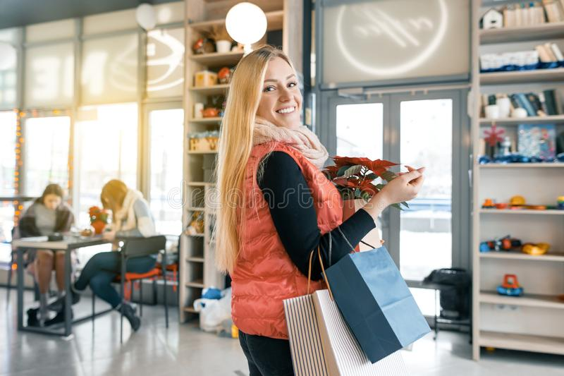 Happy smiling blonde in coffee shop with shopping bags and red poinsettia christmas flower. Winter portrait, girl in woolen scarf. With Christmas shopping stock photography