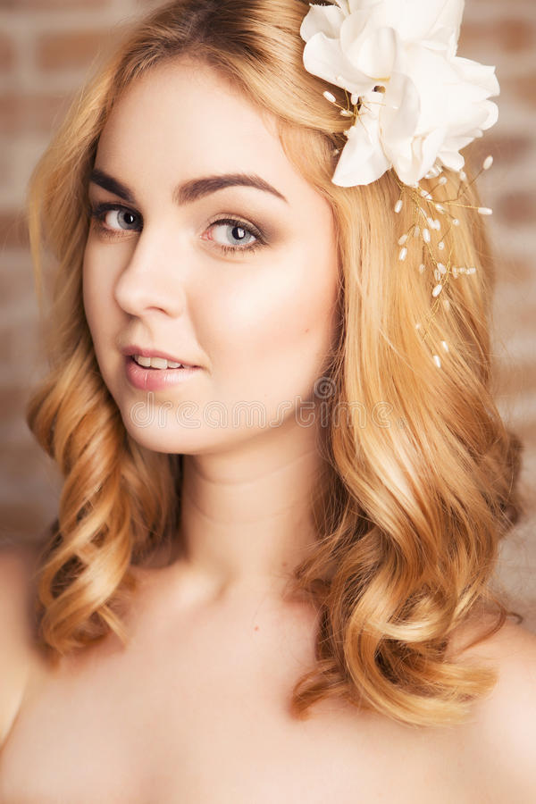 Happy smiling blonde woman with curly hairstyle and natural make. Up and lily flower in her hair posing showing her make up. fresh skin, sensual poses royalty free stock photos