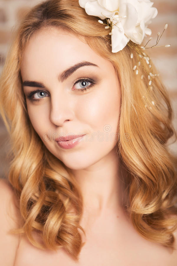 Happy smiling blonde woman with curly hairstyle and natural make. Up and lily flower in her hair posing showing her make up. fresh skin, sensual poses royalty free stock images