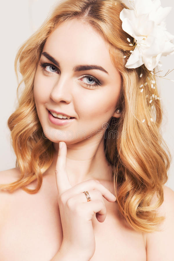 Happy smiling blonde woman with curly hairstyle and natural make. Up and lily flower in her hair posing showing her make up. fresh skin, sensual poses. hand ( stock image