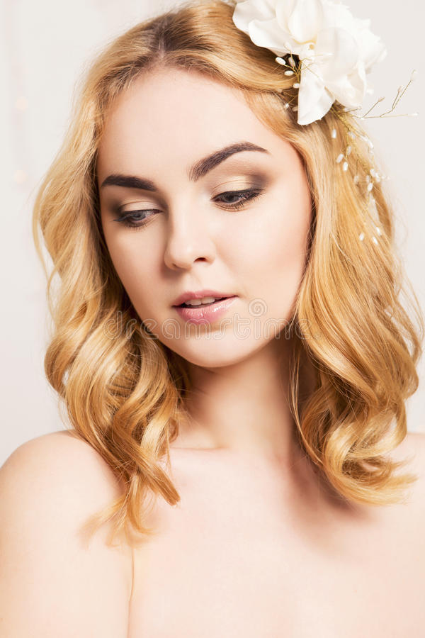 Happy smiling blonde woman with curly hairstyle and natural make. Up and lily flower in her hair posing showing her make up. fresh skin, sensual poses royalty free stock image