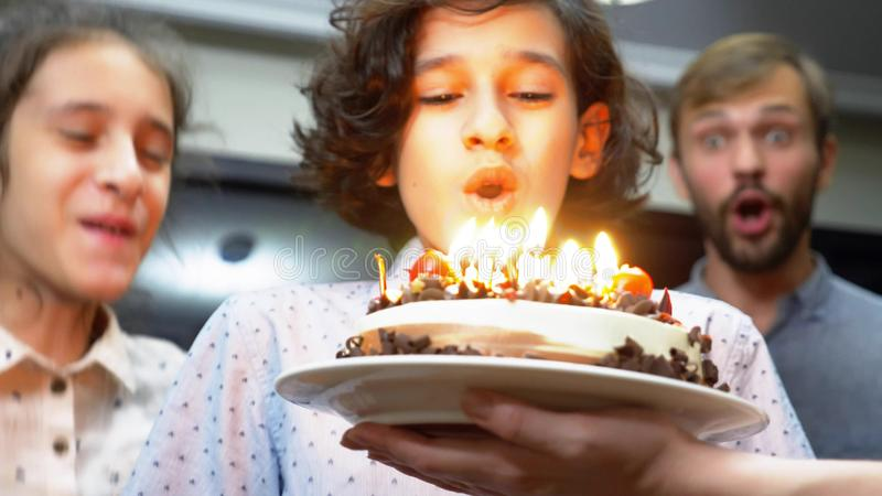 Happy smiling boy blowing candles on her birthday cake. children surrounded by their family. birthday cake with candles.  royalty free stock photography