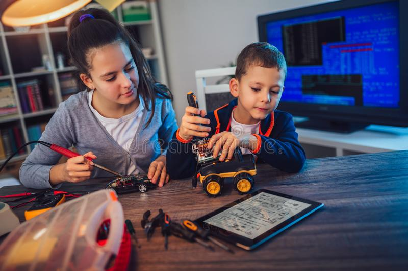 Happy smiling boy and girl constructs technical toy and make robot royalty free stock photo