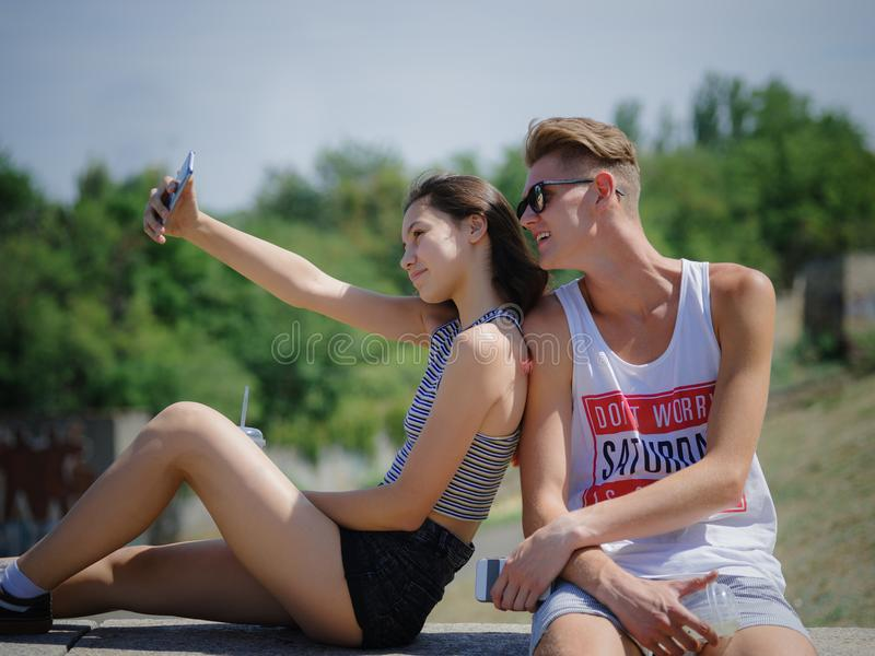 Happy smiling boy and girl on a park background. Boyfriend and girlfriend taking pictures. Progressive youth concept. stock image