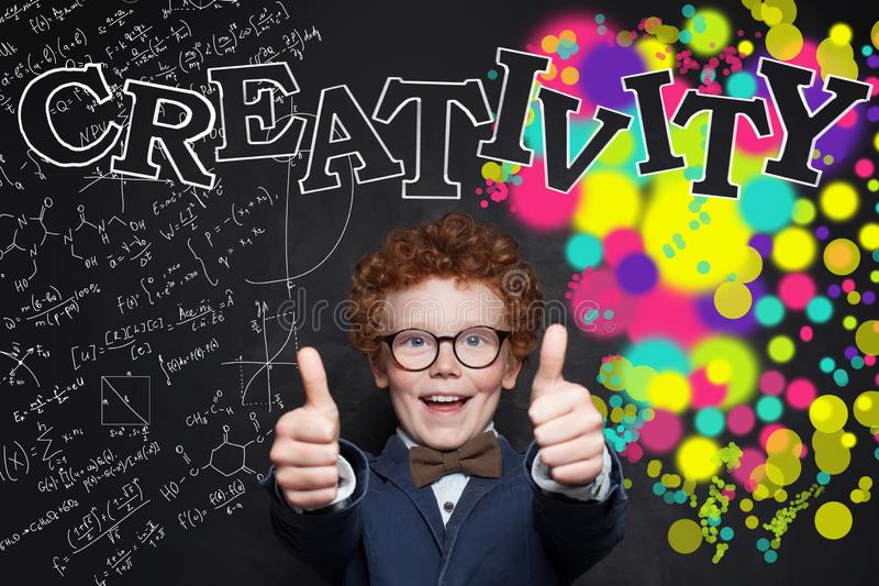 Happy smiling boy in glasses with thumb up. Kid indoors of the class room with blackboard on a background stock photography