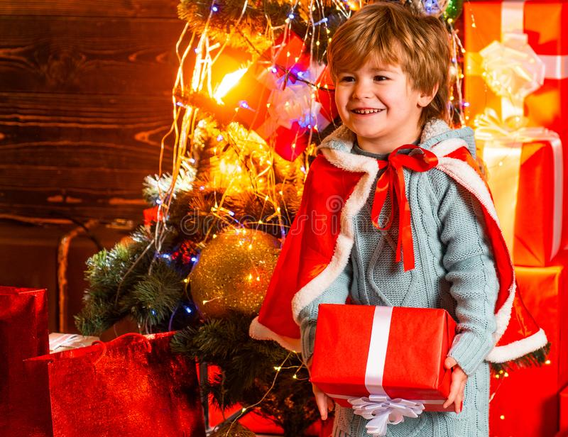 Happy smiling boy holding his Christmas present. Surprised kid at New Year decorated background. Family winter holidays. And people concept. Childhood moments stock photo