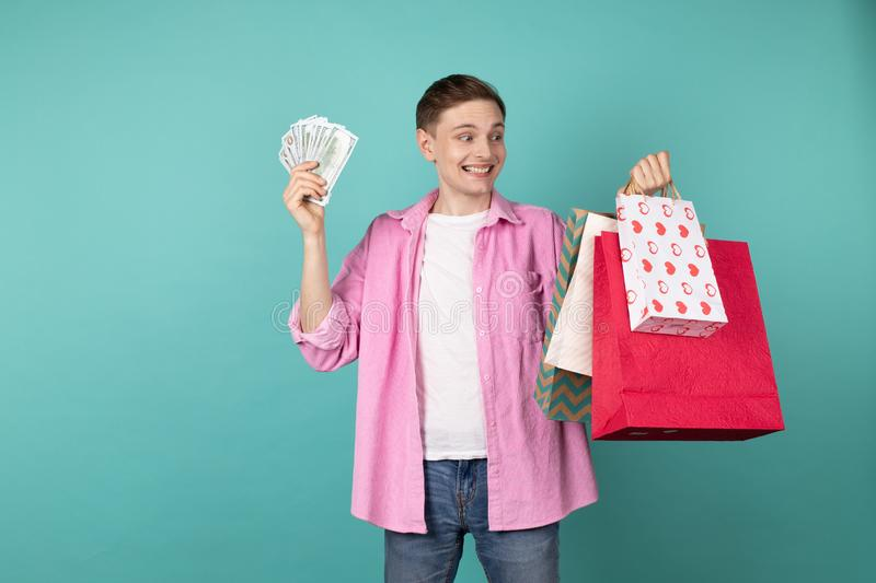 Happy smiling boy in pink shirt with money and shopping backs in hands royalty free stock photography