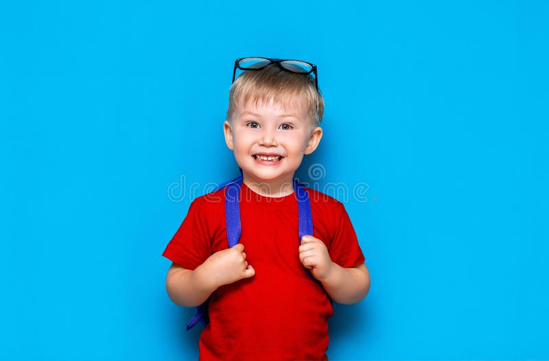 Happy smiling boy in red t-shirt with glasses on his head is going to school for the first time. Child with school bag. Kid on stock photo