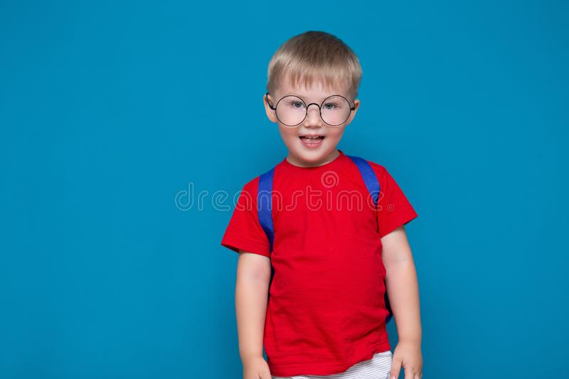 Happy smiling boy in red t-shirt in round glasses is going to school for the first time. Child with school bag. Kid on blue. Background background. Back to royalty free stock photo