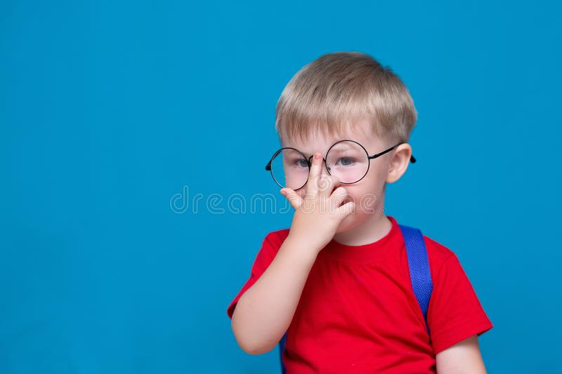Happy smiling boy in red t-shirt in round glasses is going to school for the first time. Child with school bag. Kid on blue stock image
