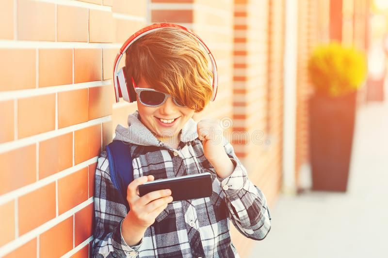 Happy smiling boy with smartphone playing game outside, over brick wall. New generation, leisure, children, technology. Schoolboy stock images