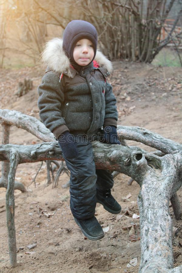 happy smiling boy in warm clothes and hat covering his neck from cold wind llooking at camera in autumn outdoor stock photography