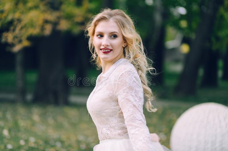 Happy, smiling bride with curly blonde hair. Portrait of beautiful girl on green nature background. Close-up stock photos