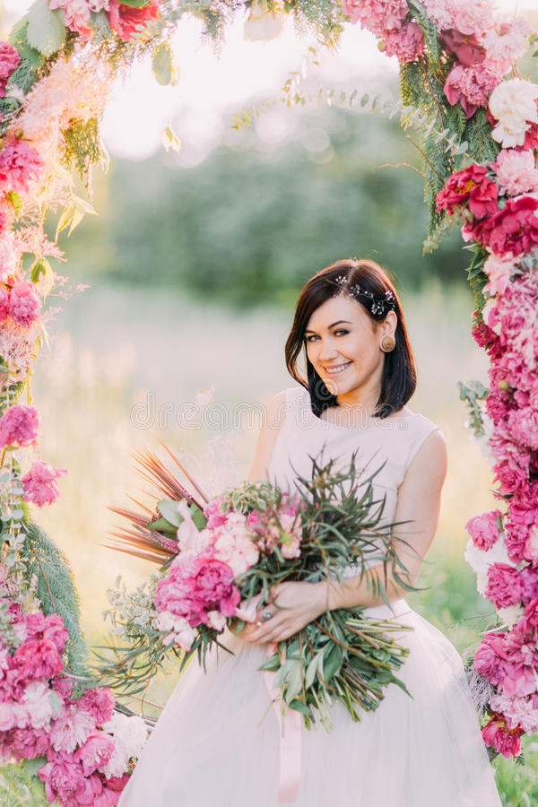 Happy smiling bride with great flower bouquet is sitting in the wedding peonies arch in the sunny park. royalty free stock image