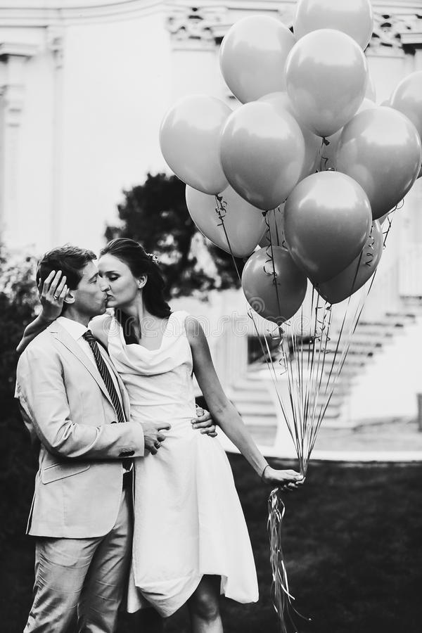 Happy smiling bride and groom holding yellow balloons background. Castle royalty free stock photo